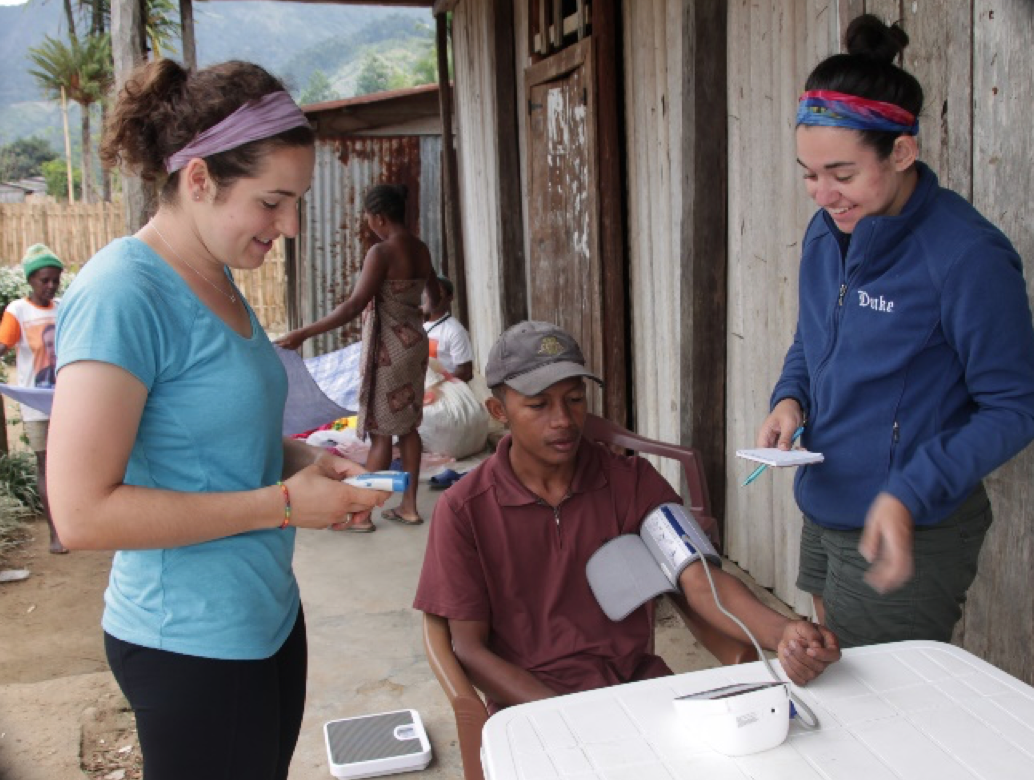 Two female Duke graduate students taking the blood pressure of a Malagasy villager