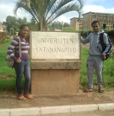two Malagasy students standing next to University of Antananarivo sign