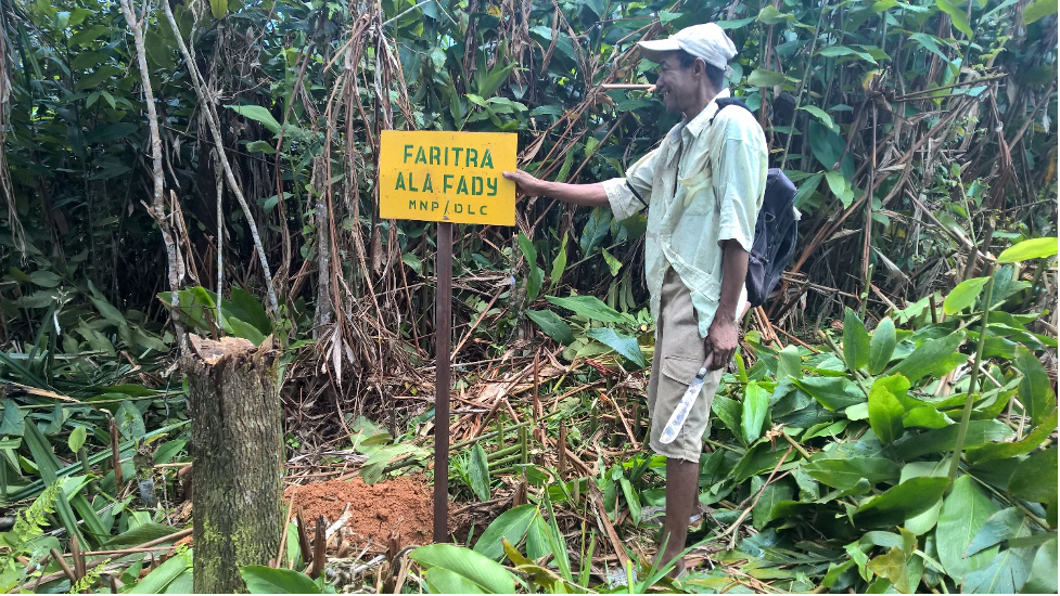 Man standing next to a sign that notes the boundary of a protected area.